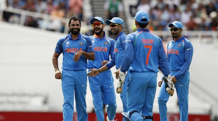 India's Mohammad Shami (L) celebrates the wicket of New Zealand's Neil Broom